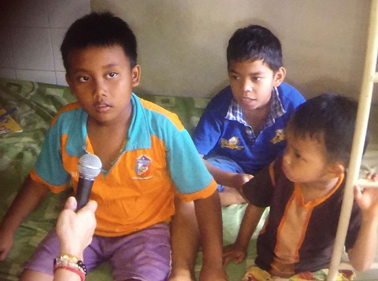 drie weeskinderen op bed.